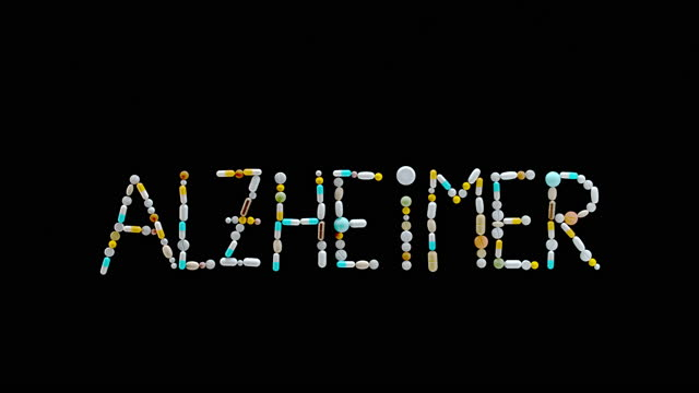 """slo mo ld inscription """"alzheimer"""" made out of colourful tablets being blown off the surface - alzheimer's disease stock videos & royalty-free footage"""