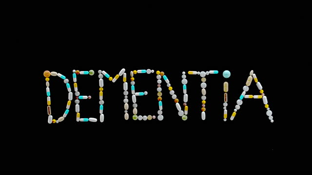 """slo mo ld inscription """"dementia"""" made out of colourful tablets being blown off the surface - dementia stock videos & royalty-free footage"""