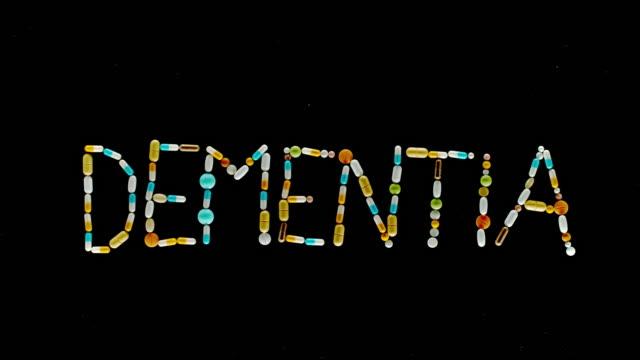 """vídeos y material grabado en eventos de stock de slo mo ld inscripción """"dementia"""" hecha de tabletas, píldoras y cápsulas de colores volando en el aire - demencia"""