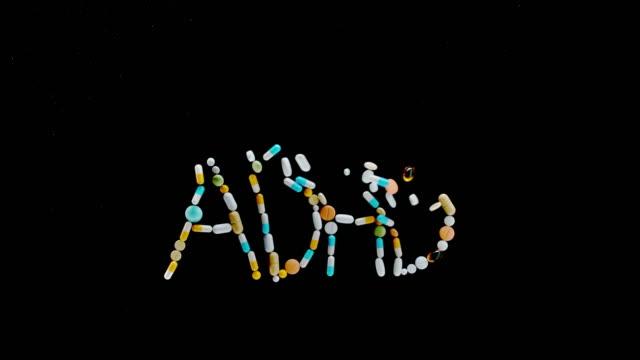 """カラフルな錠剤、錠剤、カプセルから作られたslo mo ld """"adhd""""碑文は、表面から飛び立つ - 注意欠陥過活動性障害点の映像素材/bロール"""