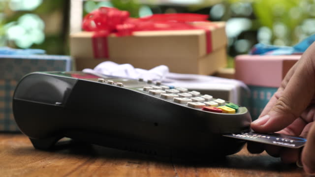 insert a credit card into credit card reader with gift box - money back guarantee stock videos & royalty-free footage