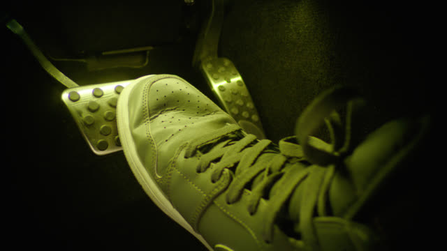 insert grey hi-tops/blue jeans presses gas and brake pedals with alternating feet - accelerator pedal stock videos & royalty-free footage