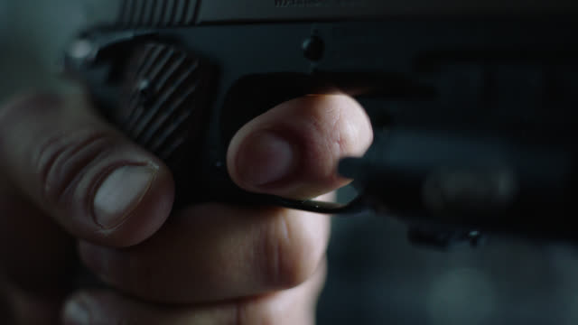 insert male hand pulls trigger on hand gun - trigger stock videos & royalty-free footage