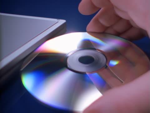 cd inserted into a laptop cd-rom abdrive - okänt kön bildbanksvideor och videomaterial från bakom kulisserna