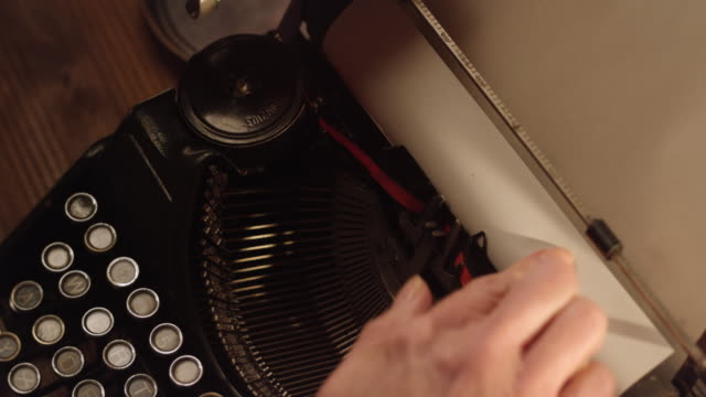 DS Inserting a white sheet of paper into typewriter