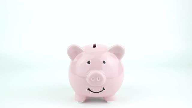 inserting coins in pink piggy bank - savings stock videos & royalty-free footage