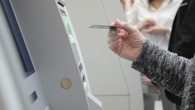 Inserting credit card into ATM, handheld shot