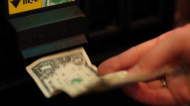 inserting dollar bill into arcade game machine - one us dollar note stock videos & royalty-free footage