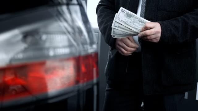 hd dolly: hineinstecken geld in ein auto gas-tank-top - tankstelle stock-videos und b-roll-filmmaterial