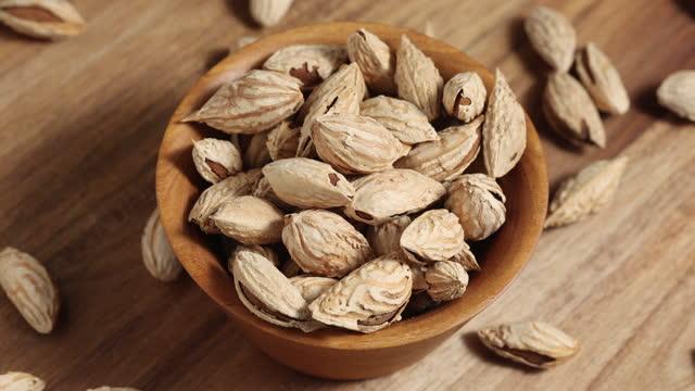 vidéos et rushes de les noix d'amandes non pelées en coque tournent dans le sens des aiguilles d'une montre, arrière-plan macro-alimentaire, vue de dessus - vitamine a