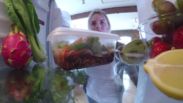 Inside a fridge, a woman takes left over chinese