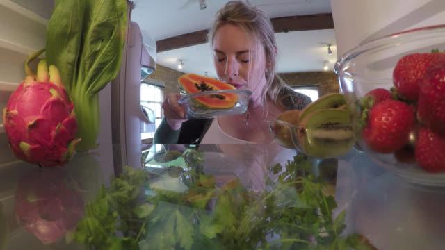 vídeos y material grabado en eventos de stock de inside a fridge, a woman takes papaya fruit out - oler
