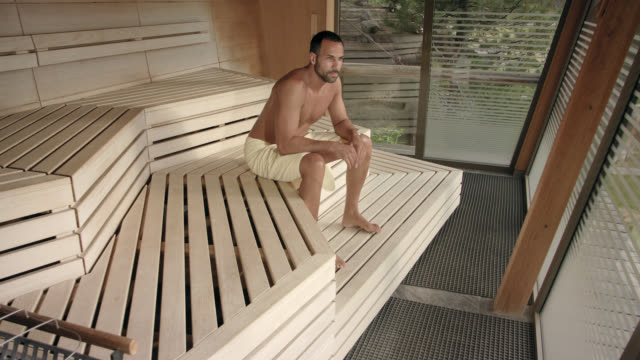 inside a hot panorama sauna – sporty buff masculine male man in his 30s enters a modern designed wooden sauna wearing a towel only and sitting down on bench enjoying the heat while purging and detoxing and sweating in the late sun of the day relaxing - wrapped in a towel stock videos and b-roll footage