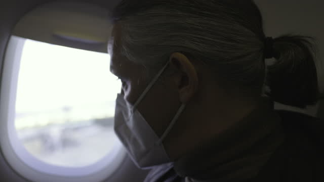 inside a plane wearing protective n95 face mask, looking out of the plane. - looking through window stock videos & royalty-free footage