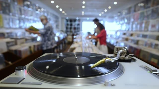 vidéos et rushes de à l'intérieur d'un magasin de disques avec les clients - disque vinyle