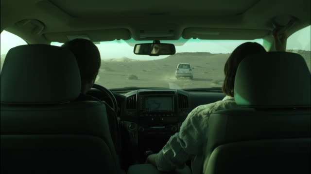 vídeos de stock e filmes b-roll de inside all terrain car following another vehicle through desert, jordan - seguir atividade móvel