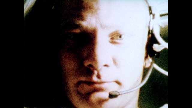 / inside apollo 11 capsule / neil armstrong checking equipment radio communication in background / workers in the command center in houston / cu neil... - 1969年点の映像素材/bロール