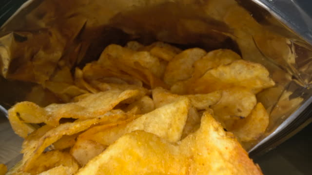 vidéos et rushes de inside bag of crisps and chips - unhealthy eating