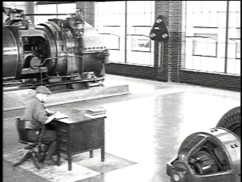 1921 pan inside of a factory for asbestos products with man sitting at a desk surrounded by sparkling machinery in big showroom / waukegan, illinois, united states - 1921 stock-videos und b-roll-filmmaterial