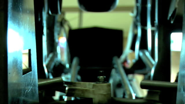 ecu inside of ball return machine behind bowling lane in focus metal bolt rotating belt fg soft multiple bowling balls moving one at a time down... - ボーリングボール点の映像素材/bロール