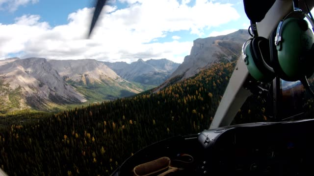 stockvideo's en b-roll-footage met binnenkant van proef die een helikopter op de herfstbos in rotsachtige bergen vliegt - red
