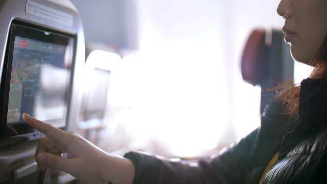 飛行機のキャビンにマルチメディアタッチスクリーンを使用して女性の乗客と飛行機の中で、スローモーション - 自動車部品点の映像素材/bロール