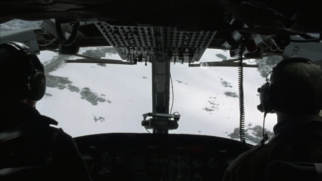 POV inside the cockpit of an aircraft flying over a barren snow-covered mountain range.