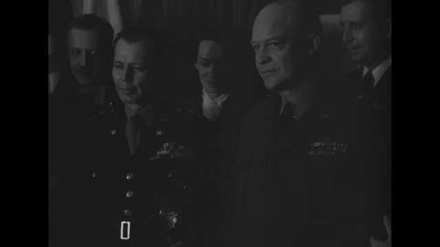 Inside the headquarters of Supreme Headquarters Allied Expeditionary Force at Reims Gen Dwight Eisenhower poses for photo opportunity with high...