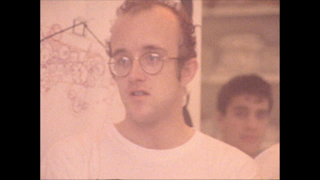 Inside the Pop Shop on Lafayette Street Keith Haring talks with Andy Warhol / Warhol leaves the shop and walks outside