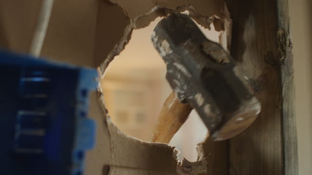 pov inside the wall of a home suddenly a sledge hammer breaks through the drywall next to a 2x4 stud and a blue electrical box. - demolishing stock videos & royalty-free footage