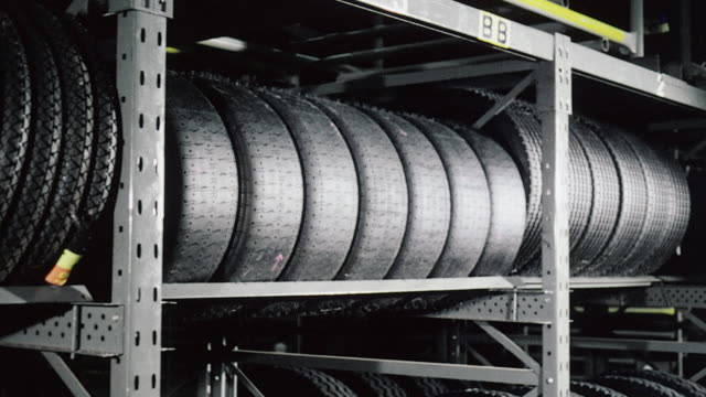 montage inside tire-making factory, with different types of tires stored in warehouse and forklift moving finished goods / bersham, england, united kingdom - tyre stock videos & royalty-free footage