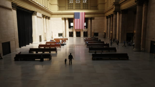 inside union station chicago. security with dog walking through the aisle. usa flag, medium wide from above. - spoonfilm stock-videos und b-roll-filmmaterial