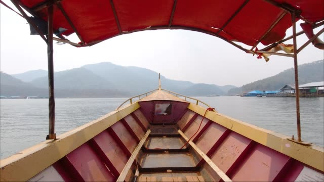 vidéos et rushes de inside view from red long boat at the lake - à bord