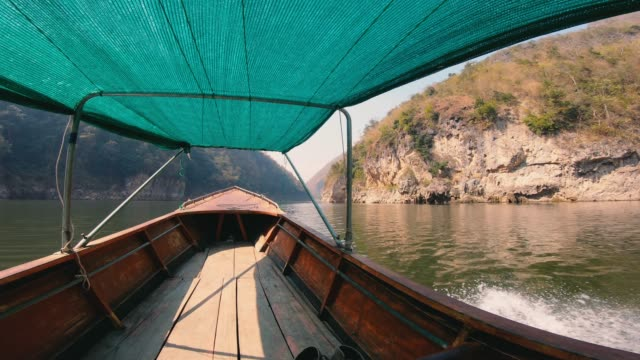 inside view of  boat driving in river in forest and mountain.summer travel
