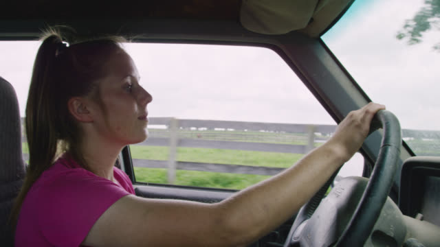 inside-the-car shot of a twenty-something woman driving a truck past pasture and farms in the country - ponytail stock videos & royalty-free footage