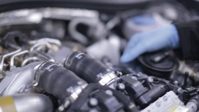 vídeos de stock, filmes e b-roll de inspecting a car engine - mecânico de carro