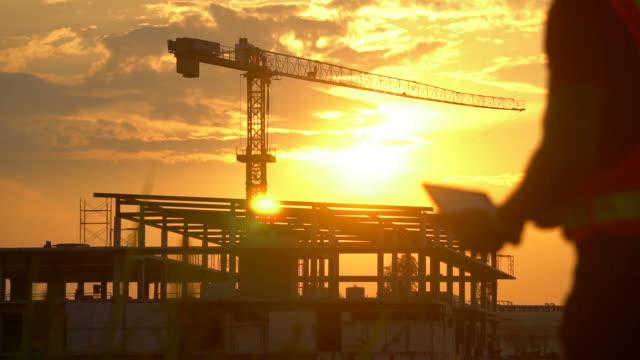 vídeos de stock e filmes b-roll de inspecting engineer in construction site at sunset - guindaste maquinaria de construção