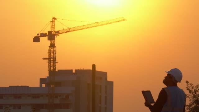 vídeos de stock, filmes e b-roll de engenheiro de inspeção no canteiro de obras ao pôr do sol - estrutura construída