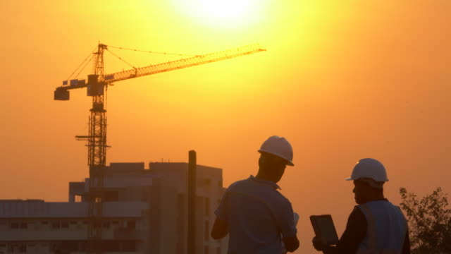 inspecting engineer in construction site at sunset - costruire video stock e b–roll