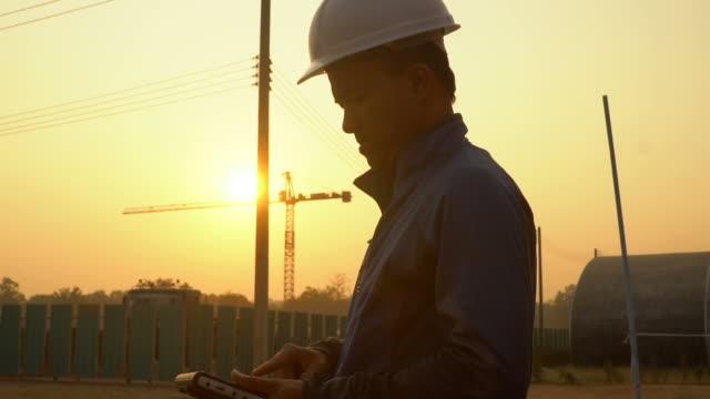 vidéos et rushes de ingénieur d'inspection avec des grues dans la construction de site - béton