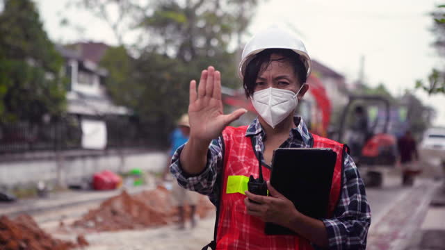 inspector construction woman worker with protective face mask working at road construction site , main water supply solution , civil engineering , stop sign , bad condition gesturing - stop sign stock videos & royalty-free footage