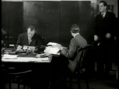 inspector finch' and 'lt. roberts' sitting at desk papers detective brings in cab driver '...well it's like this here regarding this murder...'... - anno 1949 video stock e b–roll