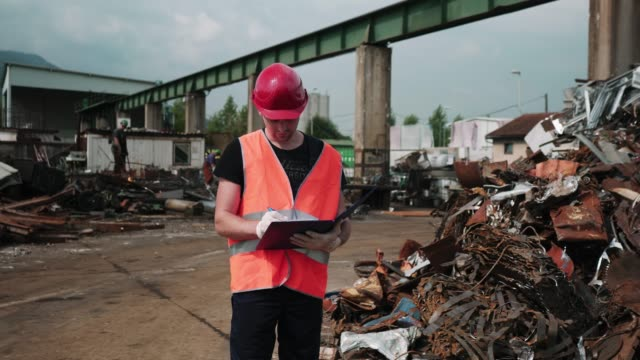 inspector standing at a pile of rusted metal, writing down something - garbage disposal stock videos and b-roll footage