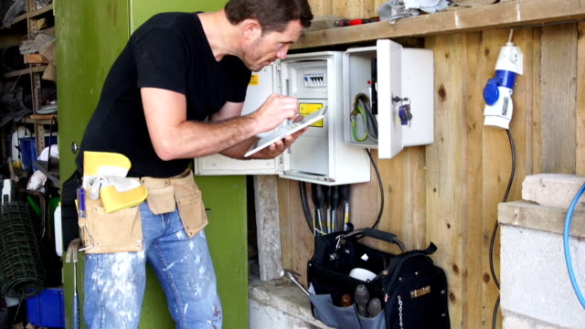 crane hd: inspector with digital tablet at fuse box - electrician stock videos and b-roll footage