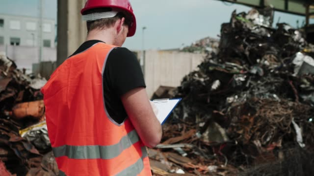 inspector writing down important notes at garbage dump - garbage disposal stock videos and b-roll footage