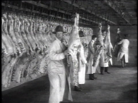 Inspectors in abattoir inspecting sides of beef that are pushed in on hooks / Camp Sherman Chillicothe Ohio United States