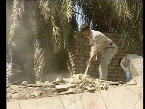 inspectors withdrawal; baghdad: lgv damage and rubble from us cruise missile hit as men sorting through in b/g man using shovel to clear rubble side... - baghdad stock videos & royalty-free footage