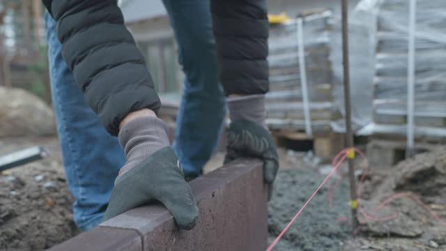 vídeos y material grabado en eventos de stock de instalación de un bordillo en un sendero. - brazo humano