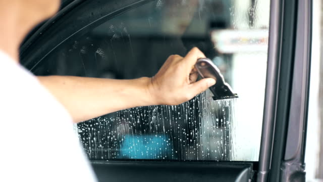 installation of car window tint, hand cleaning and scraping the window surface. - repairing stock videos & royalty-free footage
