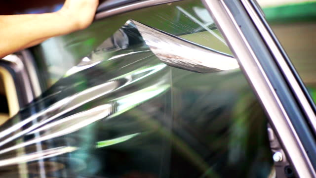 installation of car window tint, hands removing old car window film. - wrapping stock videos & royalty-free footage